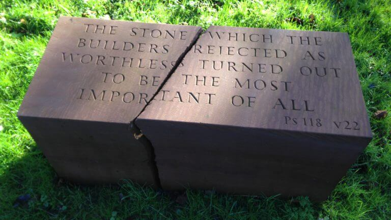 "Red sandstone foundation stone, cracked through the middle. The inscription on the top reads: ""The stone which the builders rejected as worthless turned out to be the most important of all"". From Psalms 118, verse 22"