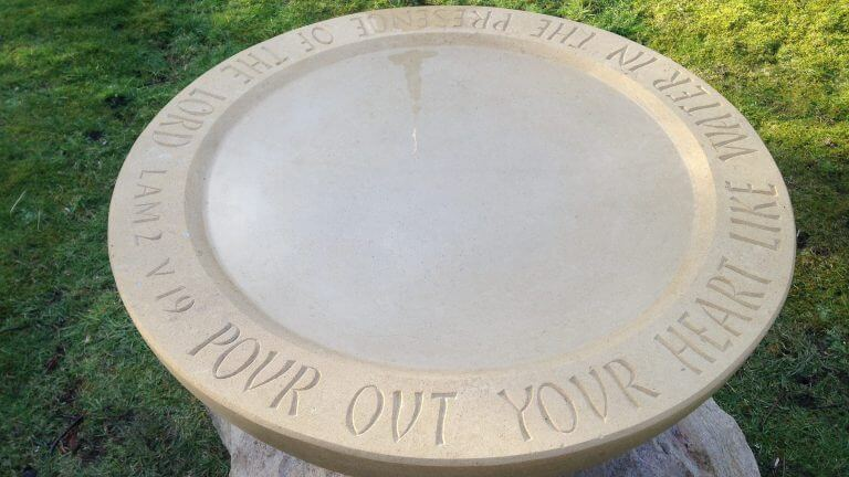 "Stone bird water table full with water and carved with the inscription: ""Pour out your heary like water in the presence of the Lord"". From Lamentations 2, verse 9"