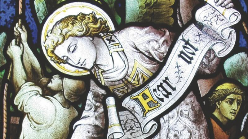 Detail of an angel holding a scroll saying 'Fear not' in a stained glass window at St James