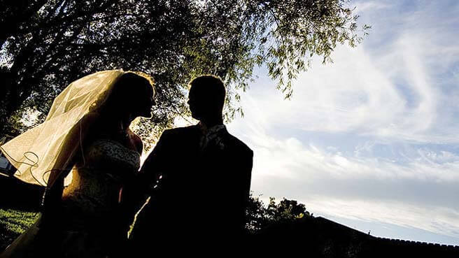 Silhouette of a newly married couple posing for photos after the wedding