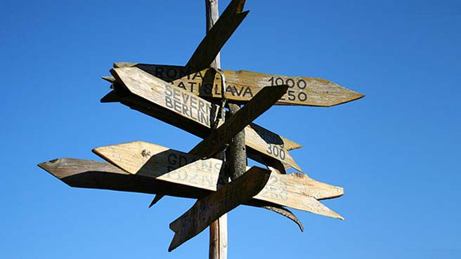 A wooden signpost with lots of signs pointing to different destinations