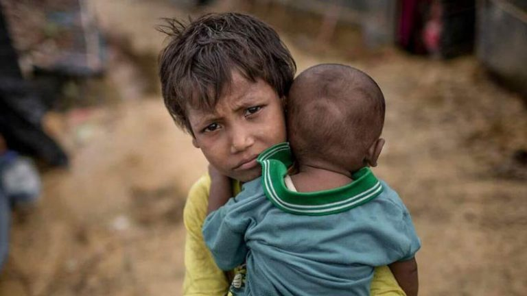 A young Rohingya refugee child carries a baby