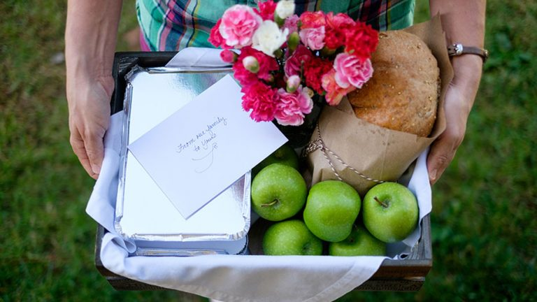 A basket laden with apples, bread, flowers, a ready-to-cook meal and a card with good wishes