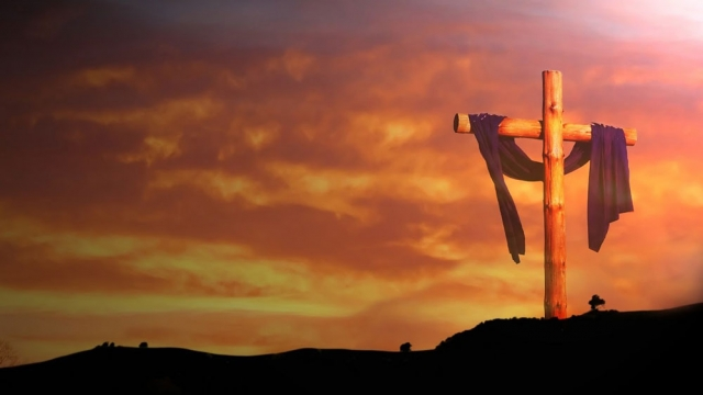 An empty cross draped with grave clothes, set against a sunrise