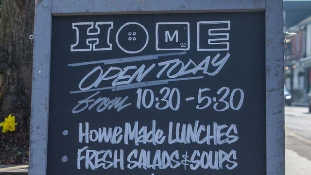 Close up of handwritten exterior sandwich board with opening times