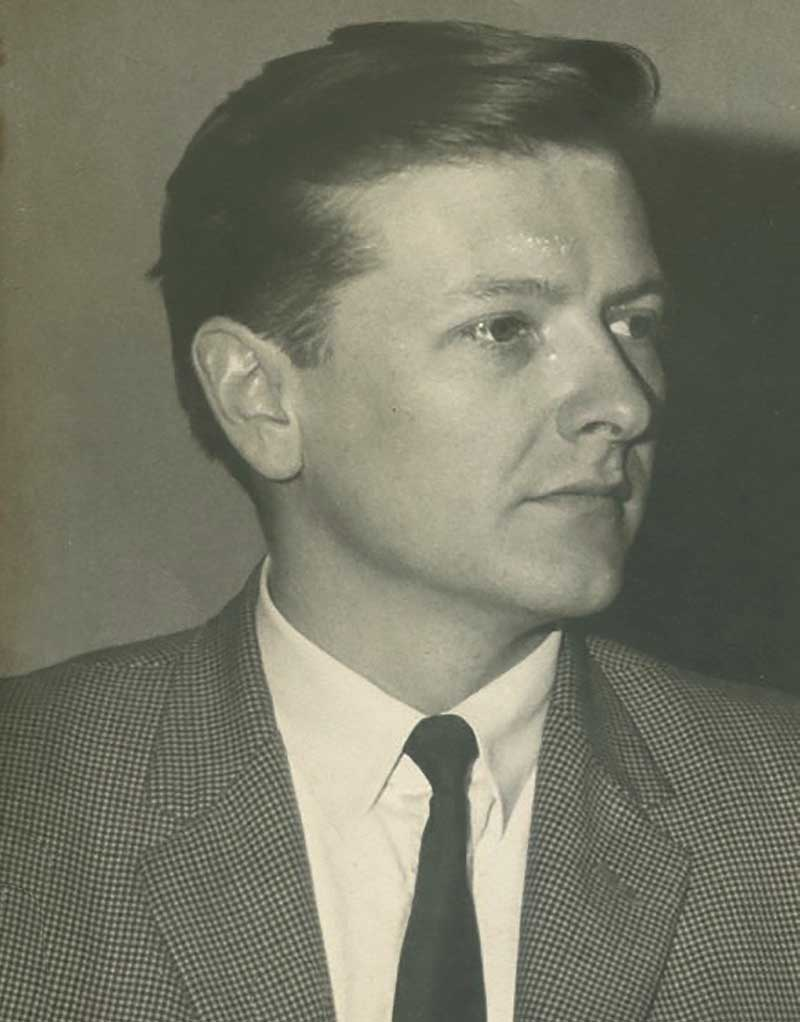 A black and white photogragh of Alex, wearing a jacket and tie