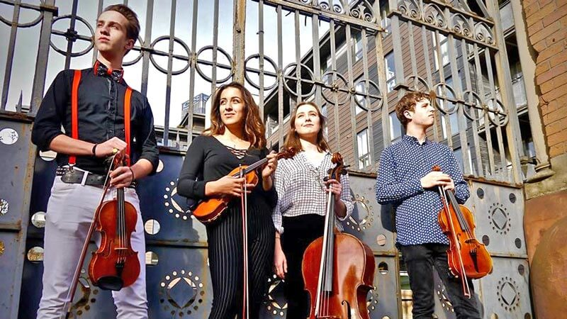Two male and two female musicians pose with their instruments in front of an iron gate in Manchester