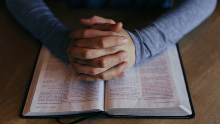 Clasped hands rest on an open bible in an attitude of prayer