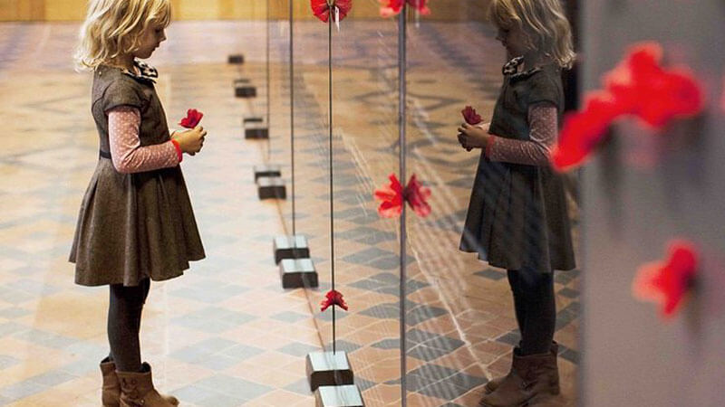 A young girls holds a red poppy as she looks carefully at the names of soldiers listed on a memorial