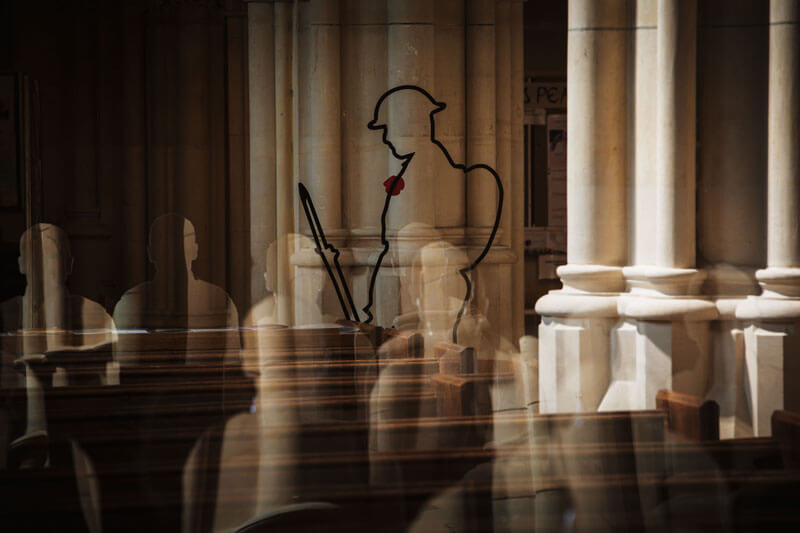 A Tommy silhouette stands in front of acrylic soldier shadows sitting in the pews at Arundel Cathedral