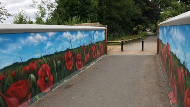 View of poppy mural on the bridge with the poppy planting just beyond