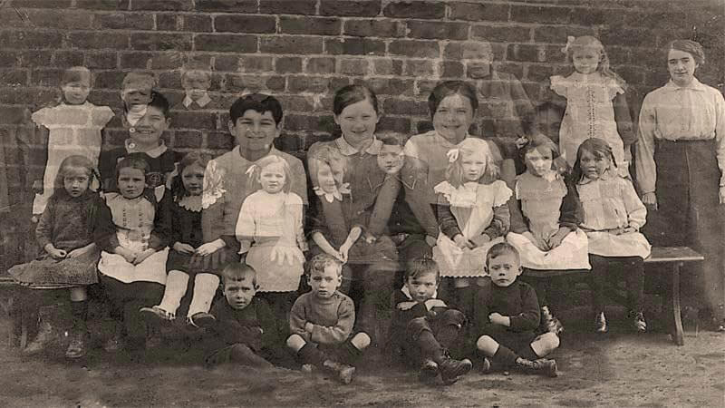 Sepia photograph primary school children from the early twentieth century with faces of current Didsbury pupils superimposed