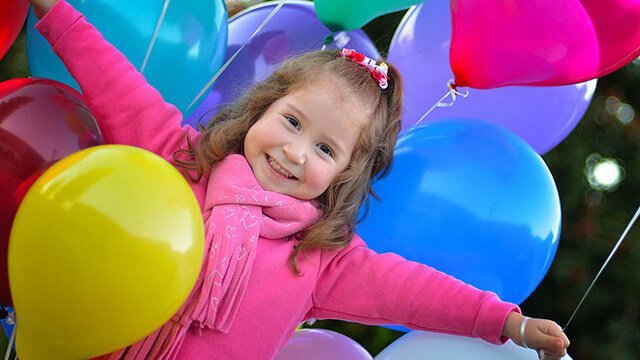 Smiling girl in pink top, surrounded by colourful balloons