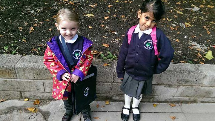 Two girls in uniform with satchels