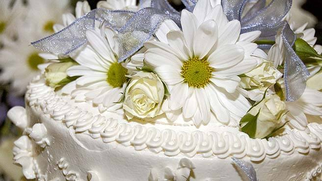 Detail of the white icing on a wedding cake, featuring roses and daisies