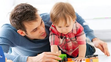 A young father and his toddler son play on the floor with wooden toys