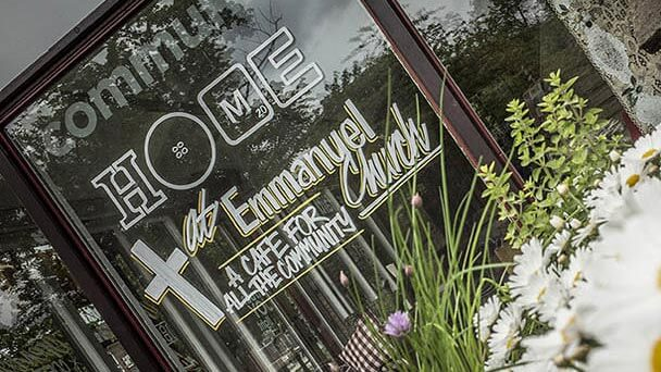Café window with the logo and other text in white signwritten lettering