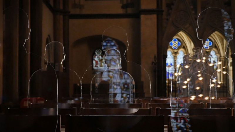 Acrylic soldier silhouettes sit in church pews