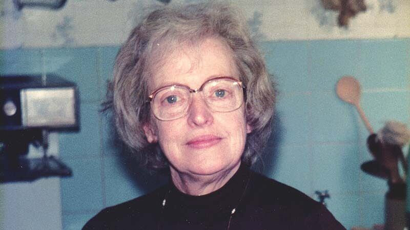 A young Marjorie, bespectacled and wearing a black polar neck top