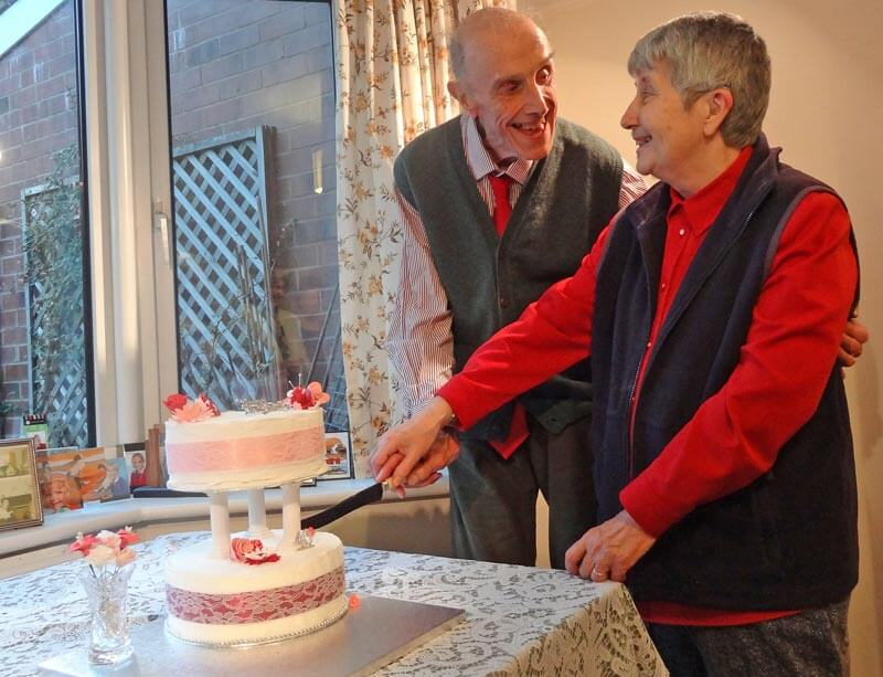 A very happy John and Margaret prepare to cut the two-tiered pink and white anniversary cake