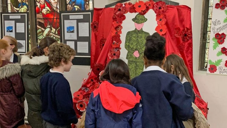 Children gather round a poppy-strewn memorial made by Didsbury CE pupils