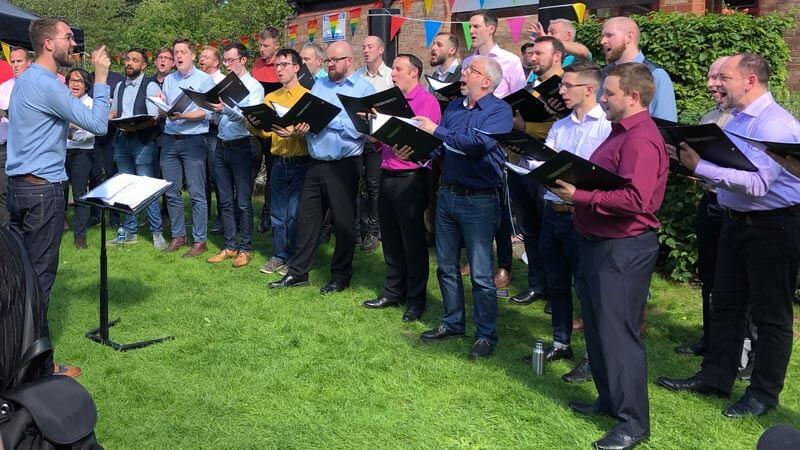 Didsbury Pride choir sings on the lawn outside Emmanuel's Parish Centre