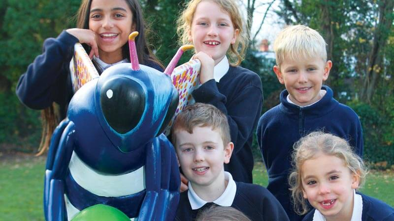 Six boys and girls from the three Trust schools pose next to a colourful sculpture of a Manchester bee