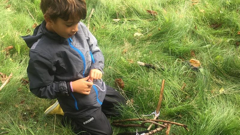 Year 3 boy tieing a knot during a Forest School session