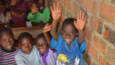 Smiling children wave to the camera