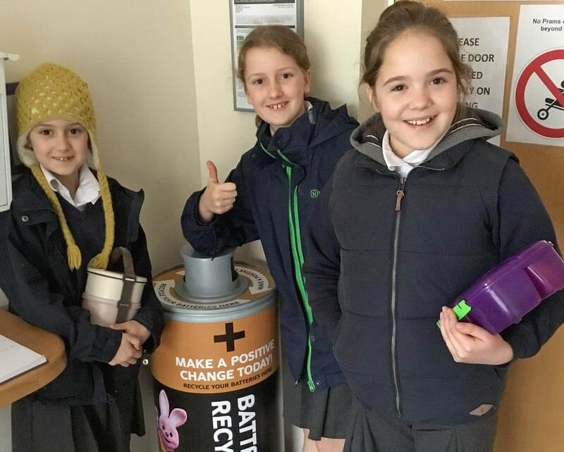 Three girls give the thumbs up for the school's battery recycling point