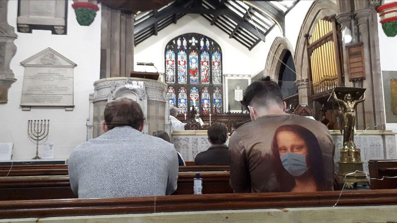 Two parishioners wearing masks at a service in St James
