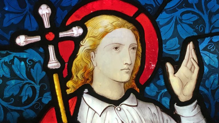 Detail of stained glass figure holding staff