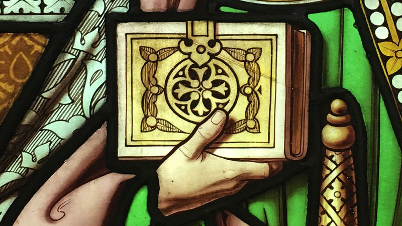 Detail of stained glass from Emmanuel depicting a hand clasping the Bible