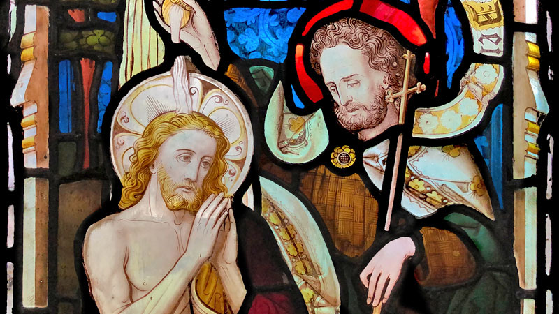 Detail of a stained glass window in St James depicting John baptising Jesus
