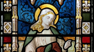 Detail of stained glass window featuring a woman with a green robe