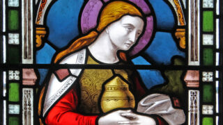 Detail of a stained glass window in Emmanuel depicting a woman holding a container